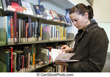 Young woman reads a book in library.
