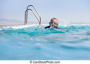 Boy Swimming In an Infinity Pool Wearing Swimming Goggles
