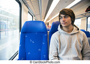 Young Man Travelling In Train, Looking Out Of Window