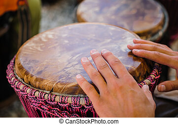 Man playing the djembe african drum outdoors