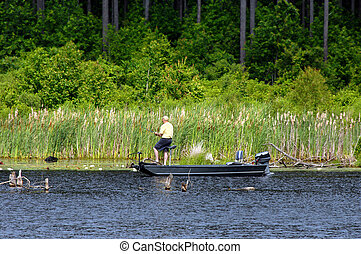 Bass Fishing on Lake - Fisherman trolls a new lake in...