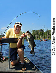 Anglers Pride - Angler kneels in his boat and holds his...