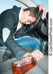 Young drunk driver sleeps in the car with bottle - Drunk man...