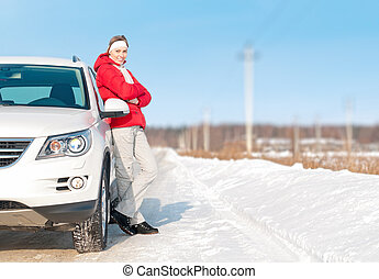 Beautiful woman standing near white car in winter.