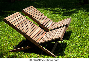 Wooden lawn chairs in the spring garden.