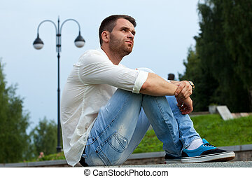 Young tired man sit on border in summer park in casual cloth