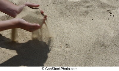 Hands full of sand falling through the fingers...