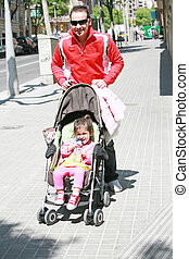 Happy father smiling with his daughter in baby carriage