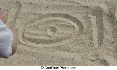 woman on the beach making self sign on the sand...