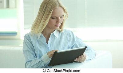 Modern ways - Blonde businesswoman working on tablet...