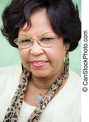 Portrait of happy elderly black lady with eyeglasses smiling...