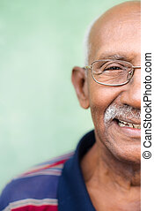 Old black man with glasses and mustache smiling