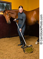 Cleaning box - Woman cleans horse box by horse fork,...