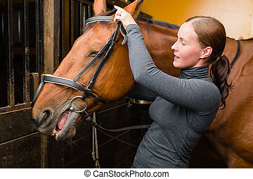 Bridle horse - Woman bridle a horse in the stall