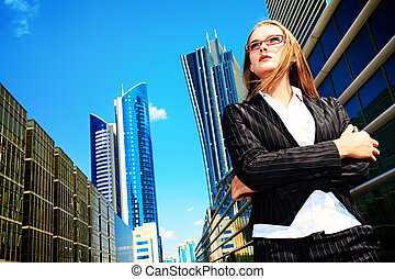 big city business - Young business woman standing in the big...