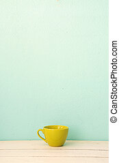 Green coffee cup on the white wood with green grunge wall...