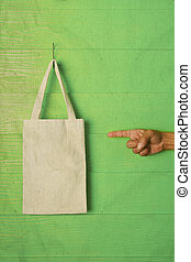 hand and finger pointing to clothes bag on green background...