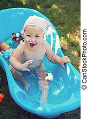charming baby having bath in the garden - charming baby...