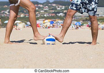 Two people stepping a ball on the beach. The picture was...