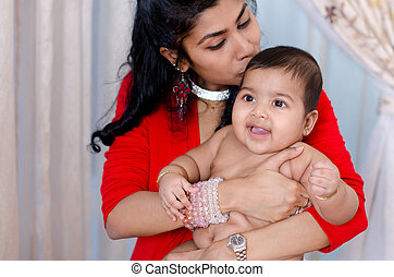 Mother kissing baby girl - Indian mother kissing her baby...