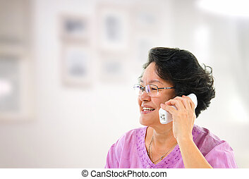 Happy phone calling - Happy mature Asian woman talking on...