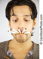 Handsome man with many cigarettes in his mouth ready to smoke addicted