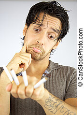 Unhappy handsome man with four cigarettes in his hand