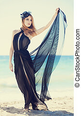 Fashion redhead girl in dress at the beach.