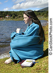 Blanket Clad - Blanket clad teenager sits besides lake in...