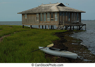 Hunting Shed and Kayak - gray kayak beached near a hunting...