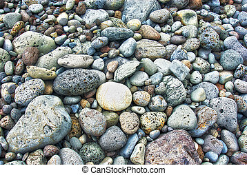 rocky beach on acores archipelago - weathered round stones...