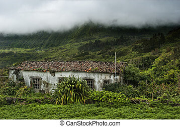 old building and cloudy mountains of flores, acores islands...