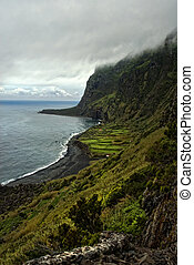 acores; flores cliff line with clouds - steep coast of faja...