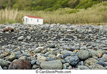 acores; deserted rocky beach with small house - coast of...