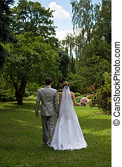 Bride and groom walking in a park