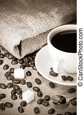cup of coffee with beans on sack