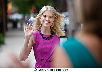 Woman Waving Hello on Street - Happy shopping woman greeting...