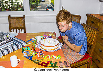boy blowing out his birthday candles at the cake