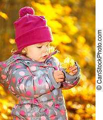 Little girl in the park - Little girl playing with leaves