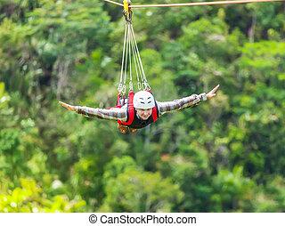 Zip-line - Men enjoying zip-line flying over the forest