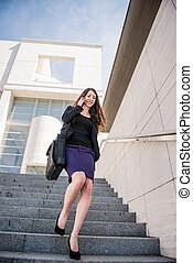 Business woman walking on stairs calling phone - Young...