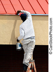 Albuquerque touchup - Man stands on top step of ladder while...