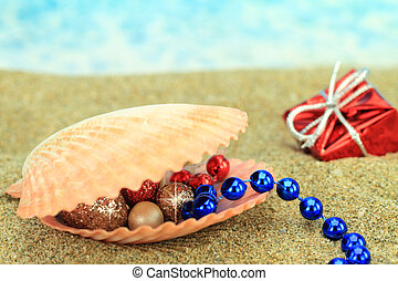 Christmas ornaments in a sea shell on the beach