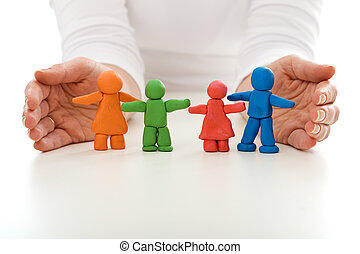 Clay people family protected by woman hands - life insurance...