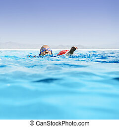 Boy in infinity pool - Young boy learning to swim in an...