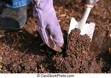 Woman gardening with gloved hand and white shovel