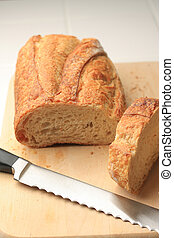 Loaf of bread on cutting board with knife
