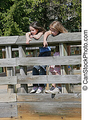two young girls peeking over a fence - children looking over...