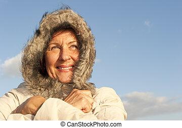 Portrait of attractive looking senior woman keeping herself...