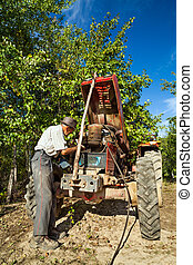 Senior farmer repairing the engine of his tractor in an orchard